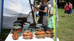Stock Video Footage of crockery pots hand craft sold in outdoor market fair and people
