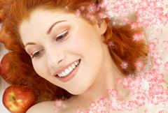 lovely redhead with red apples and flowers - stock illustration