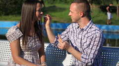 The guy makes a girl a makeover in the Park - stock footage