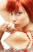Redhead with red beads looking over shoulder in water Stock Illustration