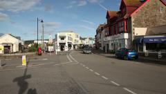 Seaside town traffic passing and pan Stock Footage