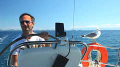 Skipper on sailing boat with seagull on Adriatic sea off the coasts of Croatia. Stock Footage