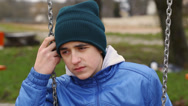 Stock Video Footage of Sorrowful teenage boy swinging in the park episode 1