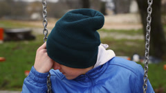 Sorrowful teenage boy swinging in the park episode 2 - stock footage