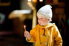 child with candle in the church - stock photo