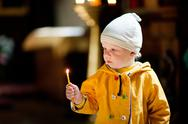 Stock Photo of child with candle in the church