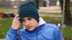 Sorrowful teenage boy swinging in the park episode 3 - stock footage
