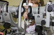 Stock Photo of girl with glasses looking at the device for vision correction