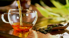 Pouring Healthy Tea. Teapot and Glass Tea Cup on the Table - stock footage