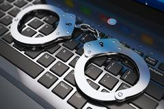 Handcuffs on laptop keyboard - stock photo
