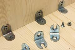 Fastening metal details at manufacturing wooden furniture Stock Photos