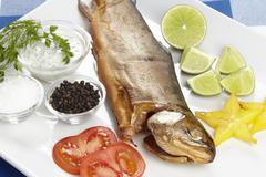 smoked trout with spices, herbals and trimming - stock photo