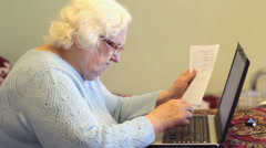 Old woman paying bills via Internet and working on laptop computer. Stock Footage