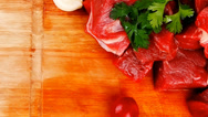 Stock Video Footage of beef meat chunks on wooden cutting plate with green hot and red