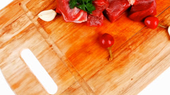 Beef meat chunks on wooden cutting plate with green hot and red Stock Footage