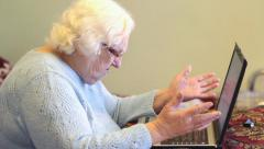Old woman and computer. Forgotten password or other computer problems Stock Footage