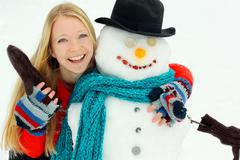 Happy woman hugging snowman outside in winter Stock Photos