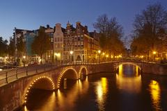 Amsterdam, netherlands - houses at a canal in the blue hour Stock Photos