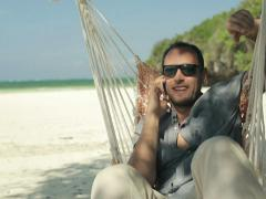 Man talking on cellphone and relaxing on hammock on exotic beach NTSC Stock Footage