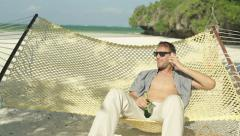 Man talking on cellphone and relaxing on hammock on exotic beach HD - stock footage