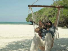 Man talking on cellphone and relaxing on hammock on exotic beach NTSC - stock footage