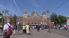 AMSTERDAM CS pedestrians in front of Central Station + tram passes Stock Footage