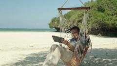 Man with laptop relaxing on hammock on exotic beach HD Stock Footage