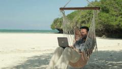 Man working on laptop while sitting on hammock, exotic beach HD Stock Footage