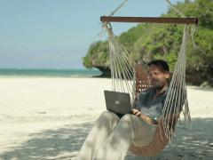 Man working on laptop while sitting on hammock, exotic beach NTSC Stock Footage