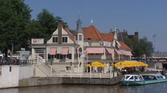 AMSTERDAM  restaurant at waterfront near CS + departing canal cruise ship Stock Footage