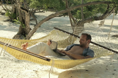 Man working on laptop while lying on hammock, exotic beach NTSC - stock footage