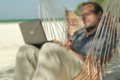 Man working on laptop while sitting on hammock, exotic beach NTSC - stock footage