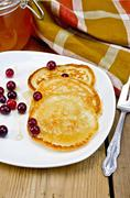 flapjacks with cranberry in a plate on a board - stock photo