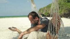 Unhappy pensive man sitting on hammock on beautiful exotic beach HD Stock Footage
