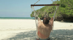 Young man relaxing, sitting on hammock on beautiful exotic beach HD - stock footage