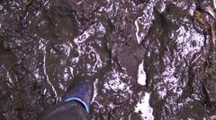 Human leg in waterproof shoes in road dirt Stock Footage