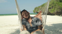Young man sleeping, resting on hammock on beautiful beach HD - stock footage