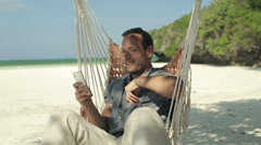 Young man on hammock using smartphone on beautiful exotic beach HD - stock footage