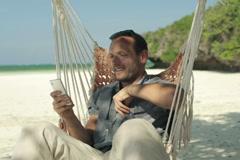 Young man on hammock using smartphone on beautiful exotic beach NTSC Stock Footage