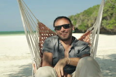 Young happy man smiling to camera, sitting on hammock on beautiful beach NTSC Stock Footage
