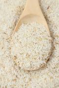 Raw rice and spoon Stock Photos