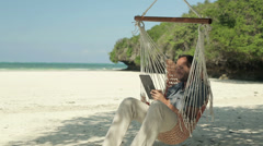 Young man with tablet computer on hammock, exotic beach HD - stock footage