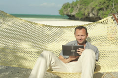Young man with tablet computer on hammock, exotic beach NTSC - stock footage