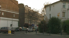 An old car drives down Shepherds bush Stock Footage