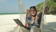 Young man with tablet on hammock smiling to camera, exotic beach HD - stock footage