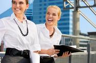 Stock Photo of two happy businesswomen with folders