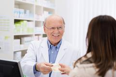 Stock Photo of helpful pharmacist dispensing medicine