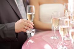 champagne in hands of bride and groom - stock photo