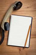 old telephone handset with notebook - stock photo