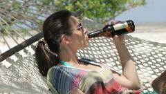Happy woman on hammock drinking beer, exotic beach HD - stock footage